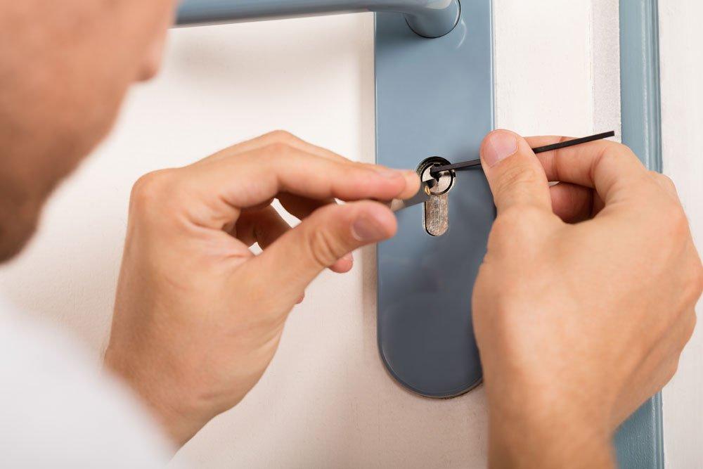 Mann holt Schlüsselbart aus dem Schloss