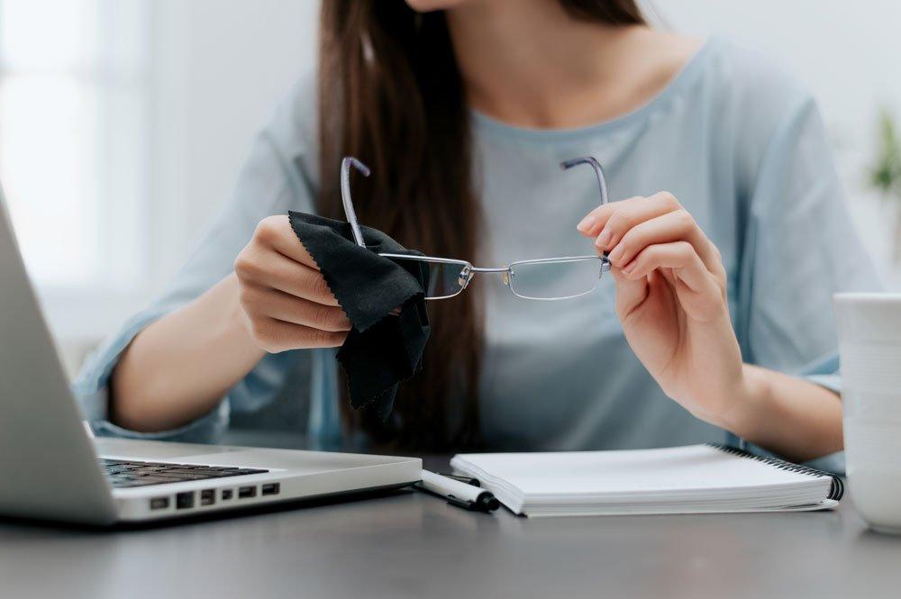 Frau putzt Brille am Laptop