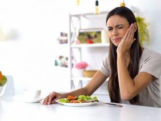 Frau hat beim Essen Zahnschmerzen