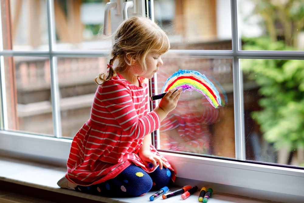 Kind malt Fensterbild mit Kreidemarkern
