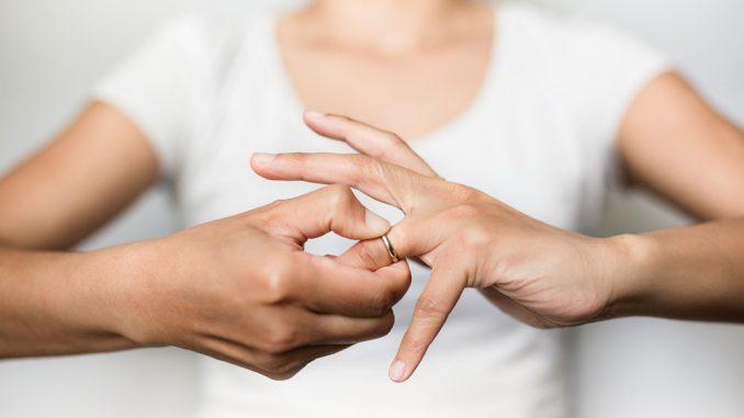 Frau versucht Ring vom Finger zu ziehen