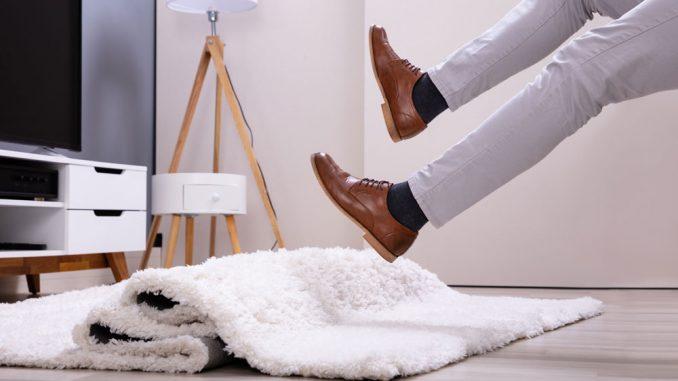 Mann rutscht auf einem Teppich weg